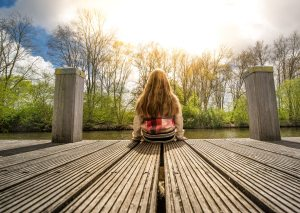 girl-sitting-water-jetty-395713